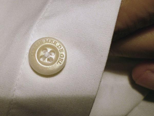Anagramme. SERGE DELSEMME - MESSE MER DE GEL. Gravure du troisième bouton, en partant de haut, de la chemise de Serge Delsemme. Gravé par Egle Bespoke, Paris. 2012. Photographie: Emmanuel Dundic