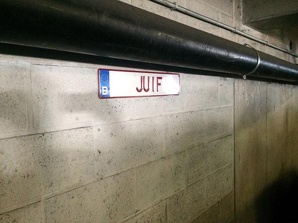 Visible au parking du Quadrilatère le 11/09/2018. Installation CENSURÉE par les autorités communales pour cause de trouble à l'ordre publique en date du 12/09/2018. Projet: 31 plaques d'immatriculations déployées sur des aires de stationnements de la ville de Huy, dans le cadre d'une exposition ayant pour thème les TABOUS et les NON-DITS. Liste complète des plaques retirées de l'espace public: PAUVRE – RICHE – POUVOIR – FAMINE – MORT – PRIER – INTELLO – VIOL – SUICIDE – MIRACULE – ARABE – JUIF – MIGRANTS – VIANDE – VEGAN – GROS – PORC – CATHO – BOBO – BONTE – FAIBLE – PARTAGE – CONARD – SALOPE – FELLATION – MASTURBER – SOUFFRIR – TORTURE – PEDOPHILE – EXCREMENT – CANNIBALE. Dédale 2018, Parcours des Arts Contemporains en milieu urbain, Huy. Parking Batta. Septembre – octobre 2018. Photographie: lavenir.net