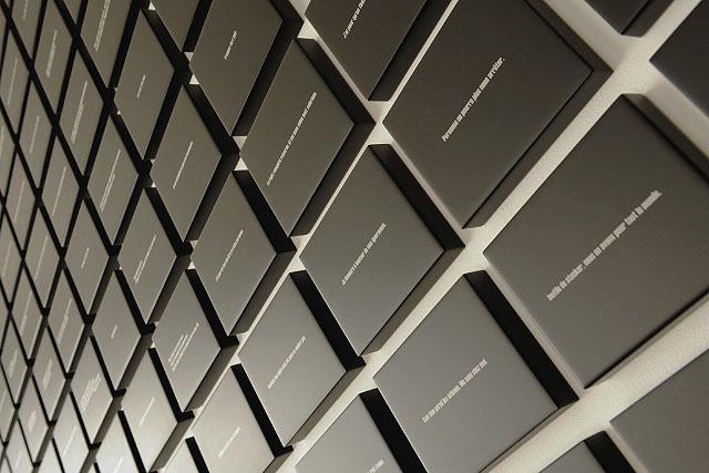 599 Blocs. Aphorismes, impression et résine sur MDF. Dimension d'un bloc: 14 x 18 x 3 cm. Ecart entre les blocs: 3 cm. Dimension de l'ensemble: variable. Galerie FLUX, Liège. Octobre 2009. Photographie: Dany Meys