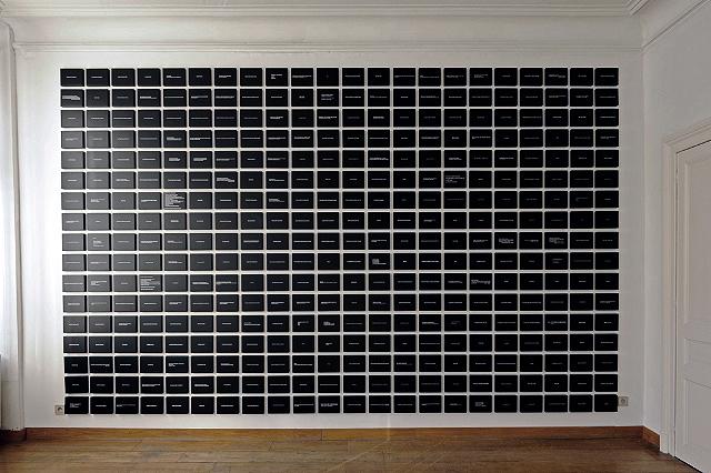599 Blocs. Aphorismes, impression et résine sur MDF. Dimension d'un bloc: 14 x 18 x 3 cm. Ecart entre les blocs: 3 cm. Dimension de l'ensemble: variable. Galerie FLUX, Liège. Octobre 2009. Photographie: Lino Polegato