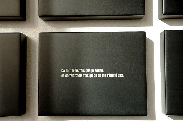 599 Blocs. Détail. Ça fait trois fois que je sonne, et ça fait trois fois qu'on ne me répond pas. Aphorisme, impression et résine sur MDF. Galerie FLUX, Liège. Octobre 2009. Photographie: Dany Meys
